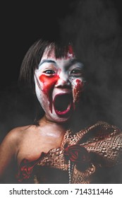 Asian kid in Thai dress with white face makeup is painted red eye look like bleeding / concept ghost kid in Halloween / ghost girl in dark background