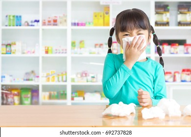 Asian kid with the tissue, she got a cold have a drugstore as background.
