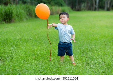 Asian kid want to catch with balloon at outdoor