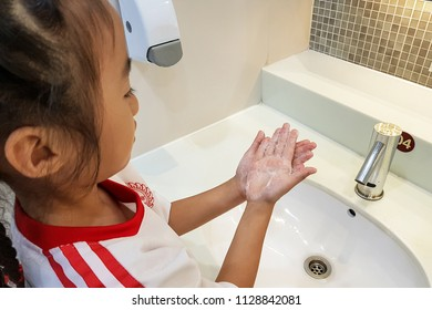 Asian kid washing their hands.