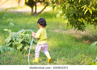 Asian kid watering plant and relaxing with home vegetable crop