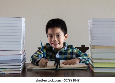 Asian kid writing something on notebook with stack of books on the wooden table