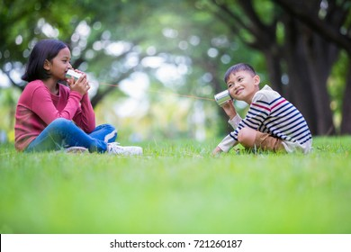asian kids brother playing canned phone in the park