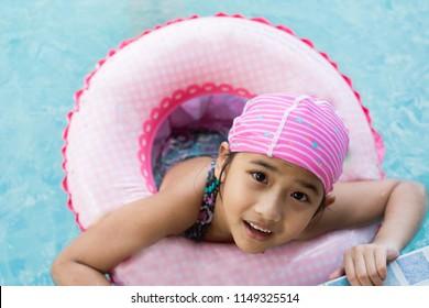 Asian Kids cute little girl Wearing rubber ring Swim in the pool