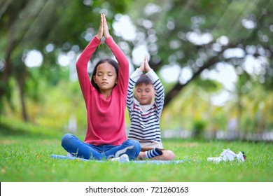 asian kids doing yoga pose in the park outdoor