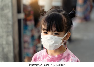 Asian kids girls wear masks on public roads to prevent the spread of COVID 19 or prevent PM2.5.