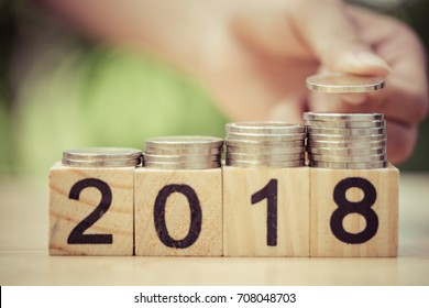 Asian kid's hand putting coins to stack of coins on wooden block with text 2018. Concept of money saving, financial, new year resolution.
