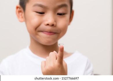 Asian kids hold with a contact lens