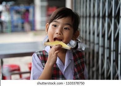 Asian kids little girl Eating bread Toast