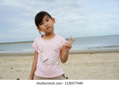 Asian kids little girl Playing on the beach
