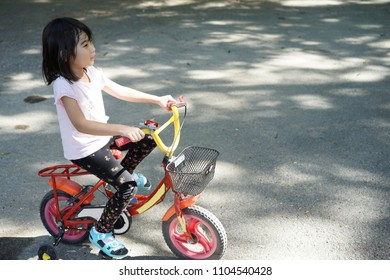 Asian kids little girl ride a bicycle smiling happy