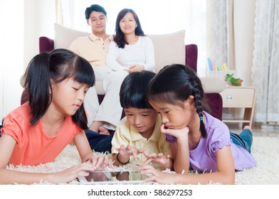 Asian kids playing tablet computer at home