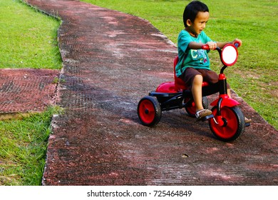 Asian Kids Riding Tricycle At Playground