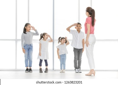 Asian kids salute to Asian woman in pink shirt, she salute backto them, they stand in front of big white window.