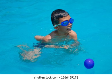 Asian kids swimming and playing in swimming pool on summer holidays time