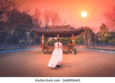 Asian korean Girls dressed Hanbok in traditional dress at sunset in South Korea.