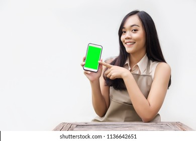 asian lady action to show blank screen on mobile phone as using application. potrait action with wood table and apron suite on white background.