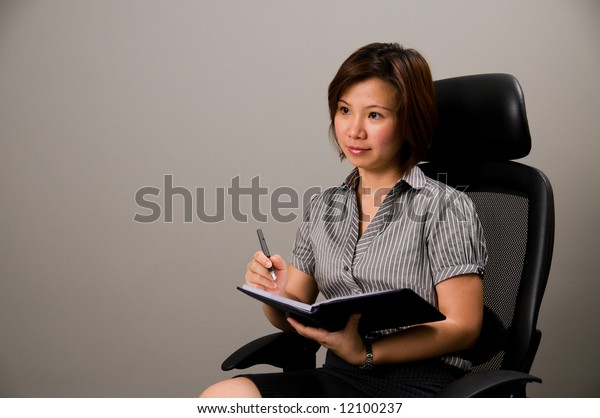 Asian lady in business attire, holding pen and organizer