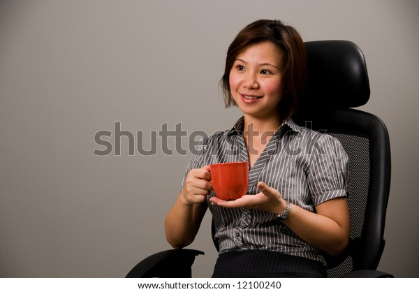 Asian lady in business attire, holding a cup of coffee