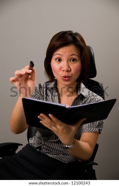Asian lady in business attire, holding pen and organizer, pointing directly at you