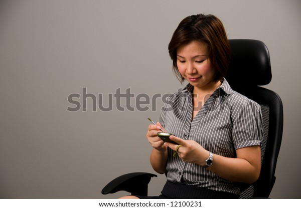 Asian lady in business attire, using a PDA (portable digital assistant)