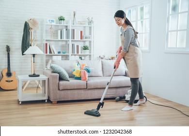 エプロンで家事をするアジア人の女性。リビングの木の床を掃除する掃除機を使う若い主婦。家で家事をする幸せな家政婦で、魅力的な笑みを浮かべた。