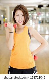 An Asian lady doing weight lifting exercise in a gym.