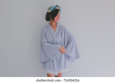 Asian lady in dressing gown with flower crown. Beautiful model girl in colorful wedding kimono robe. Female portrait of cute lady. Bridesmaid in bridal shower with copy space - vintage filter added