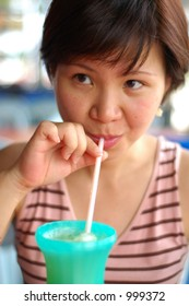 Asian lady drinking iced coffee from a straw