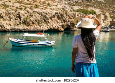 An asian lady enjoys the view over the waters of Xlendi Bay at Gozo Island, part of the maltese archipel
