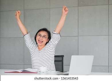 An Asian lady happy and throwing her hands up in excitement in an office or home environment.