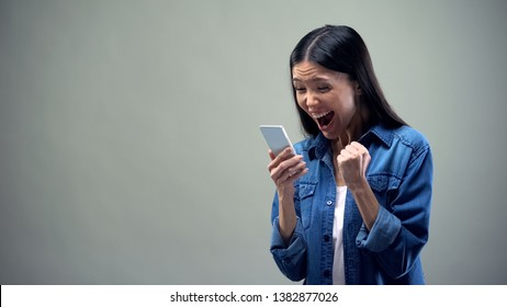 Asian lady holding smartphone, sincerely rejoicing, favorable tariffs for calls