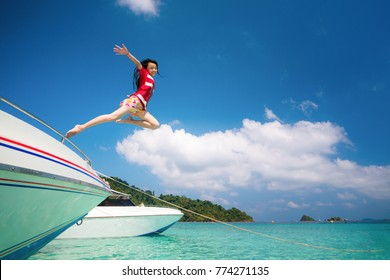Asian lady jump and fly to sky between travel the Thailand sea, Koh Kood and Mak island is island in Thailand