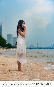 Asian lady Lonely woman standing absent minded and looking at the sea