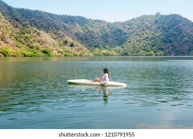 Asian lady paddling the kayak on the lake in satonda island. Sumbawa, Indonesia