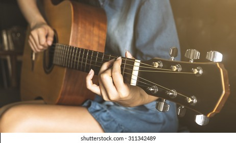 Asian Lady playing guitar with vintage look