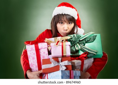 Asian lady with red Christmas outfit carrying lots of presents