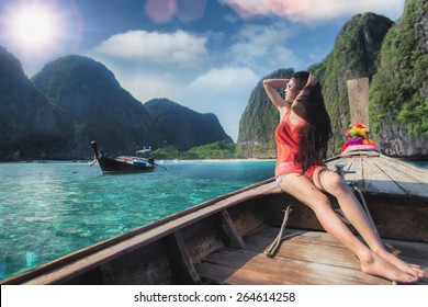 Asian lady relax on long tail boat at maya beach, Phi Phi island near Phuket in Thailand