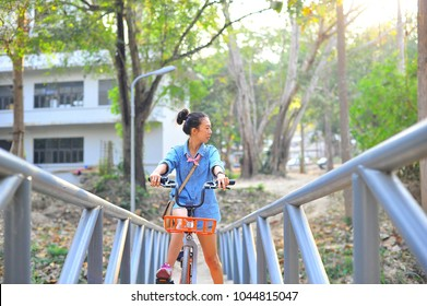Asian lady riding public bicycle through urban area in the park.Summer vocation.