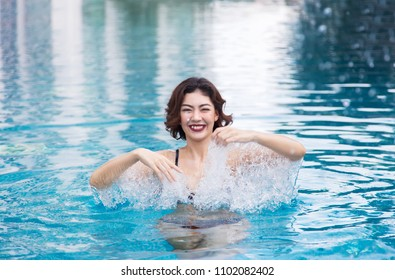 asian lady smile in water swimming pool with copt space. relax in holiday on swimming pool concept