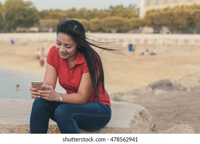 Asian lady smiling while using her mobile phone near the beach
