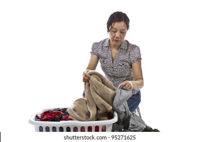 Asian lady sorting laundry in basket while wearing causal clothing on white background