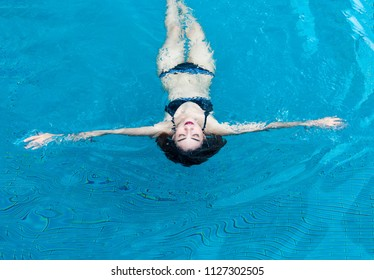 asian lady in swimming suite playing water posting on water pool. Relax in holiday concept