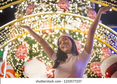 Asian lady thinking with night light decoration in santa hat