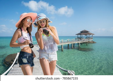 Asian lady travel resort in Kood island togather and take photo in wooded bridge to harbor, This immage can use for travel, resort, beach, summer and holiday concept