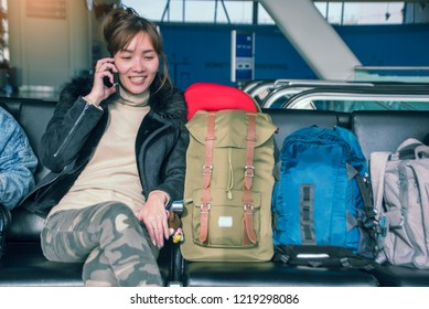 Asian lady traveler talks with a friend while waiting at the airport with three backpack.