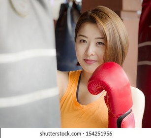 An Asian lady waring red glove practicing boxing.