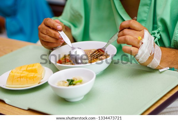 Asian  lady woman patient eating breakfast healthy food with hope and happy while sitting and hungry on bed in hospital.