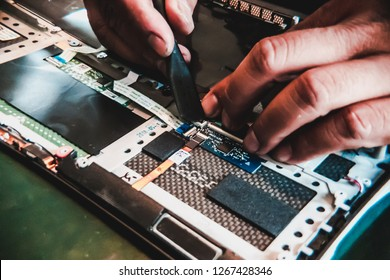 Asian laptop repair technician plugging in a ribbon cable which connect circuit boards in a laptop together