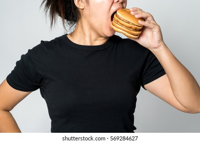 Asian Large girl eating a hamburger isolated in white